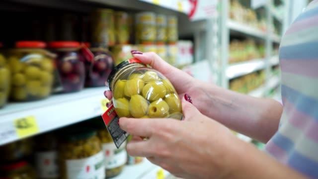 Closeup-caucasian-woman-hands-near-shop-shelves-choosing-marinade-green-olives-in-grocery-market