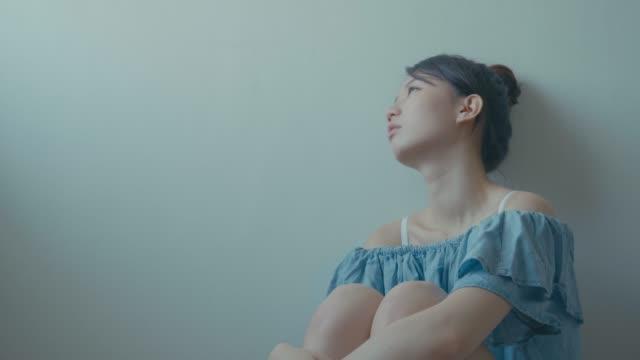 Sad-woman-sitting-alone-in-a-empty-room