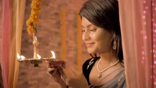 Un-tiro-lento-mo-de-mujer-feliz-en-un-luces-ropa-tradicional-una-lámpara-de-suspensión-metal-en-una-casa-decorada-con-luces-y-flores