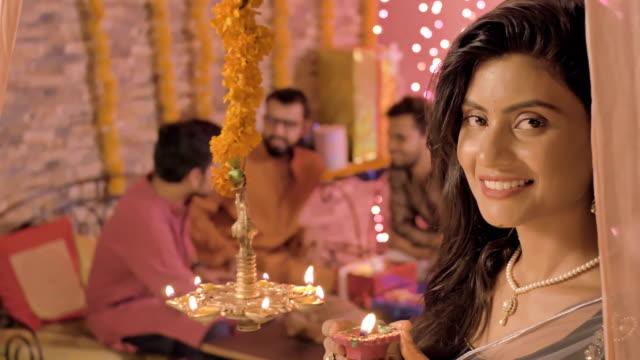 Una-hermosa-joven-en-adornos-sonriendo-mientras-la-iluminación-de-una-lámpara-de-aceite-y-un-sari