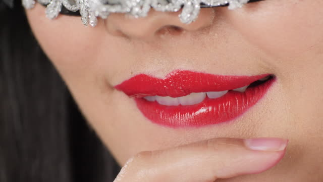 Macro-closeup-of-Sexy-woman-wearing-masquerade-mask-flirting-at-party-over-silver-glitter-background-slow-motion