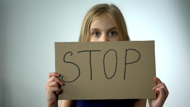 Chica-muestra-la-señal-de-stop-protección-social-de-prevención-de-la-violencia-doméstica-de-los-niños