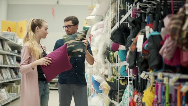 Young-married-couple-are-disputing-in-a-shop-choosing-decorative-pillows