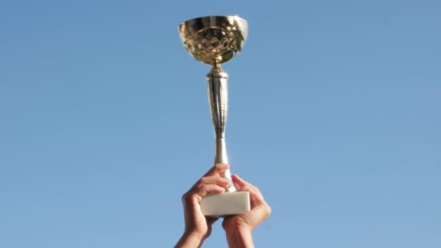 Golden-glänzend-in-der-Sonne-der-Pokalsieger-gegen-den-blauen-Himmel