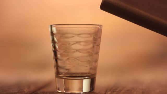 Pouring-a-whiskey-shot-on-a-shot-glass-using-a-metal-hip-alcohol-flask-closeup-macro