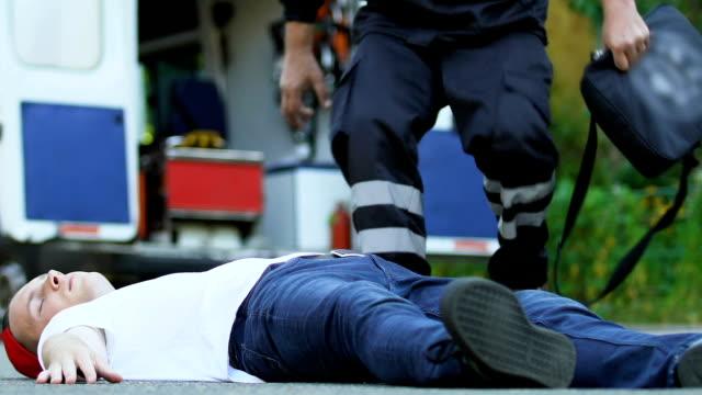 Equipo-paramédico-a-hombre-en-carretera-de-primeros-auxilios-después-del-accidente-ambulancia-
