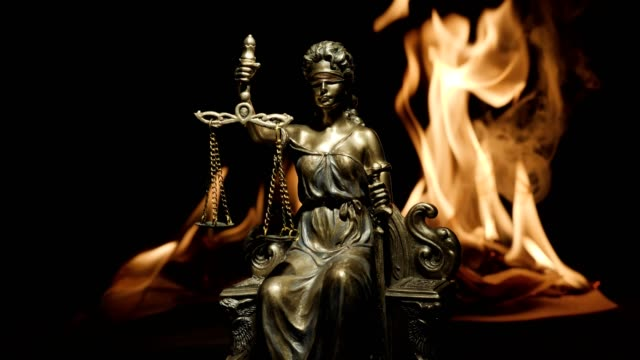 Statue-of-Lady-Justice-on-the-background-of-the-flame-of-a-burning-book