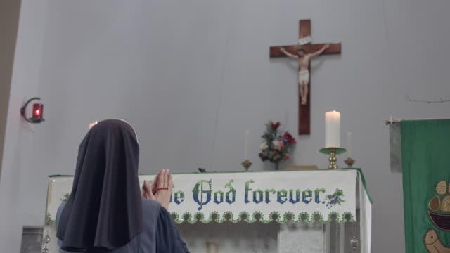 Hermana-religiosa-celebración-de-rosarios-y-arrodillarse-ante-el-altar-