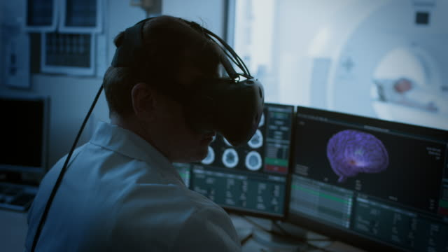 Futuristic-Concept:-In-Medical-Control-Room-Doctor-Wearing-Virtual-Reality-Headset-Monitors-Patient-Undergoing-MRI-or-CT-Scan-Procedure-Computer-Displays-Show-3D-Brain-Model-with-Possible-Tumor-