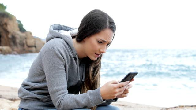 Sad-girl-receiving-bad-news-online-on-the-beach
