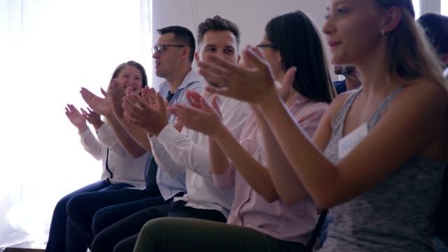 glückliches-Publikum-von-Erfolgsmenschen-Gruß-Lautsprecher-auf-Coach-training