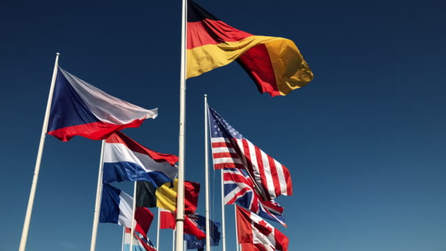 National-flags-together-flying-in-slow-motion-on-blue-sky-background