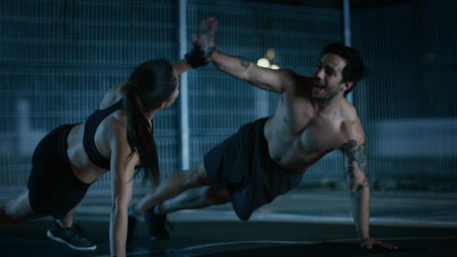 Sonriente-pareja-feliz-Fitness-atlético-haciendo-Push-Up-ejercicios-y-dar-cinco-alta-Entrenamiento-se-realiza-en-una-cancha-de-baloncesto-al-aire-libre-cercado-Imágenes-de-la-noche-después-de-la-lluvia-en-una-zona-residencial-del-barrio-