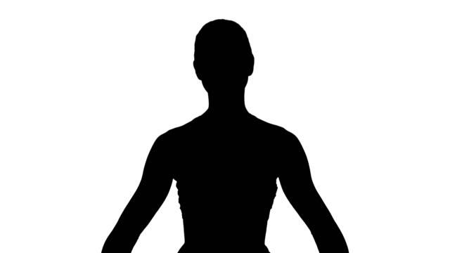Silueta-atractiva-joven-practicando-yoga-sentado-en-ejercicio-Gomukasana-pose-de-cara-de-vaca-mientras-que-a-fotografiar