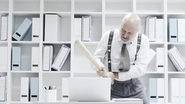 Betonte-der-Geschäftsmann-seinen-Laptop-mit-einem-Schläger-zertrümmern