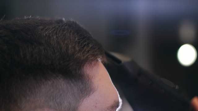 Barber-drying-male-hair-in-hairdressing-salon-Close-up-hairdresser-blowing-man-hair-with-dryer-in-barbershop-Male-hairstylish-doing-hairdo-in-beauty-studio