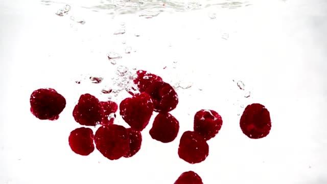 Una-frambuesa-madura-se-cae-al-agua-con-un-montón-de-pequeñas-burbujas-Video-de-baya-sobre-fondo-blanco-aislada