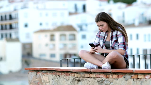 Adolescente-triste-llorando-después-de-leer-el-texto-en-un-teléfono