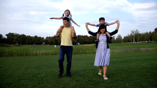 Cheerful-asian-parents-carrying-kids-on-shoulders
