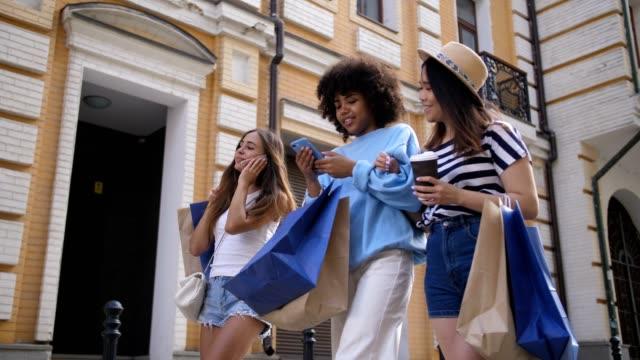 Multi-étnicas-chicas-con-los-teléfonos-después-de-ir-de-compras