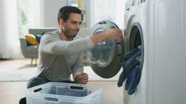 Handsome-Serious-Young-Man-in-Grey-Jeans-and-Coat-Sits-in-Front-of-a-Washing-Machine-at-Home-He-Loads-the-Washer-with-Dirty-Laundry-Bright-and-Spacious-Living-Room-with-Modern-Interior-