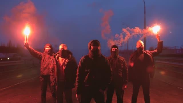 Grupo-de-hombres-jóvenes-en-pasamontañas-con-la-llamarada-roja-de-la-señal-que-camina-en-el-camino-debajo-del-puente