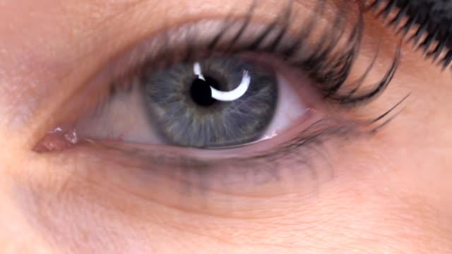 blue-eyed-woman-applying-mascara-closeup-macro