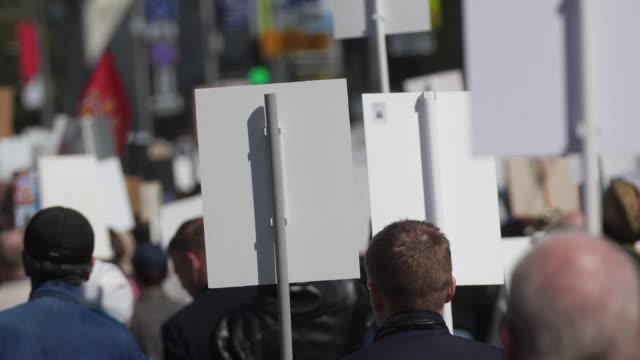 Activistas-multitudinarios-en-un-mitin-con-carteles-están-en-la-bandera-de-la-carretera-caminando-Europa-