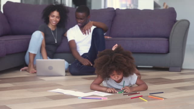 Kid-drawing-parents-using-notebook-spending-time-on-heated-floor