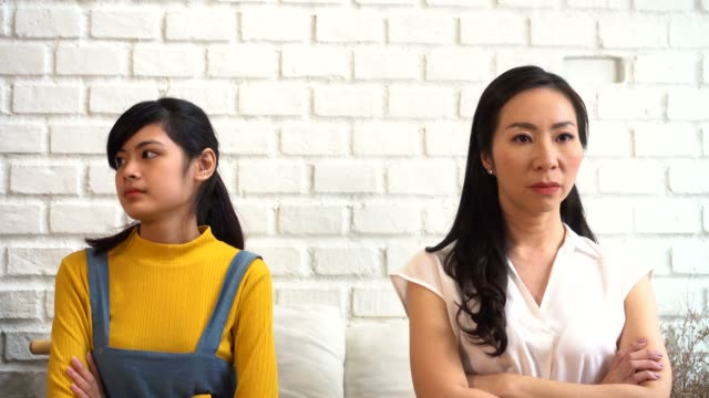 Displeased-Asian-females-sitting-on-sofa