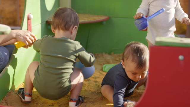 Three-Toddlers-Playing-Outdoors-in-Sand-Pit