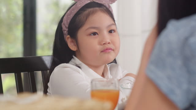 Asian-Japanese-daughter-bored-with-food-Lifestyle-kids-sad-dislike-food-upset-breakfast-meal-in-the-kitchen-at-home-in-the-morning-Slow-motion-shot-