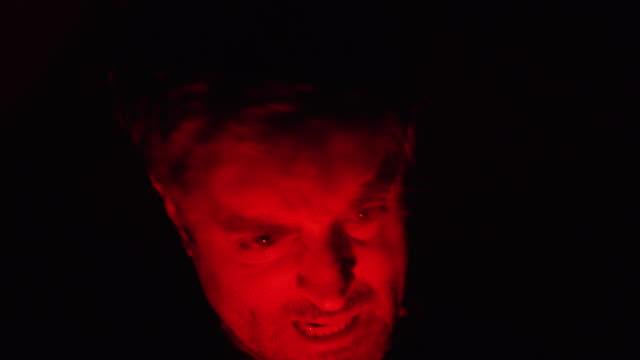 Disparos-aterradores-de-un-hombre-poseído-de-rabia-gritando-y-molesto-Conceptos-de-horror-ira-paranormales-y-de-Halloween-Grabado-en-la-cámara-roja-No-hay-límite-a-la-variación-de-negro-