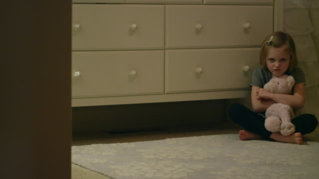 Angry-young-girl-sitting-on-her-bedroom-floor-alone-holding-and-hitting-a-stuffed-animal