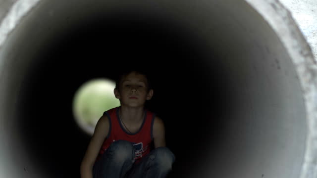 Muchacho-adolescente-triste-sentado-solo-esconderse-dentro-de-un-túnel-de-drenaje-lonely-boy-sin-hogar-refugiados