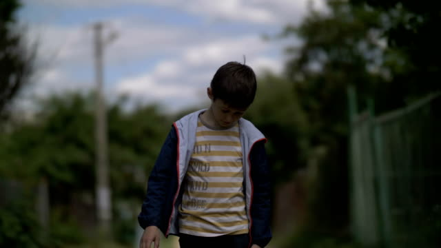 muchacho-triste-solitario-caminando-por-la-carretera-de-la-aldea-con-la-cabeza-abajo-niño-travieso-ruffian