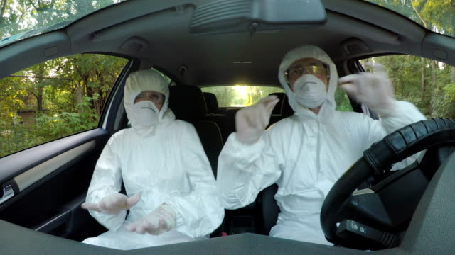 Funny-concept-of-two-young-hazmat-scientists-workers-in-car-dancing-and-driving-to-contaminated-location