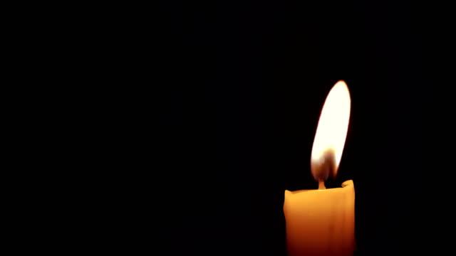 primer-plano-de-la-vela-quema-con-brillo-chispa-de-fuego-de-llama-sobre-fondo-negro-con-espacio-de-copia-de-texto-evento-festivo