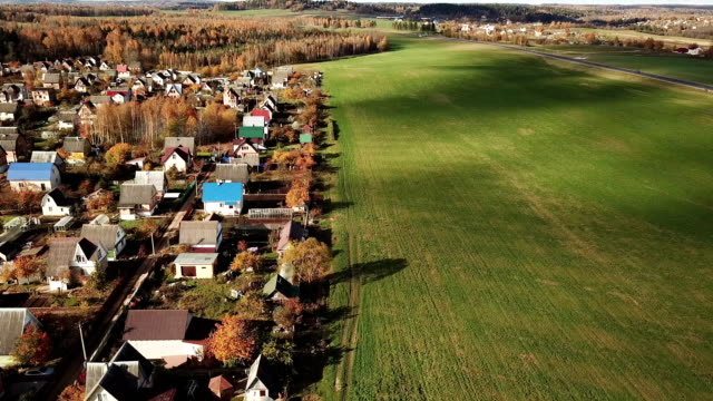 Schöne-kleine-Dorf-in-der-Nähe-von-grünen-Wiese-in-den-herbstlichen-Wald-