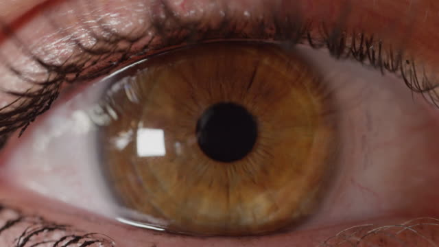 SLOW-MOTION-CLOSE-UP:-Unrecognizable-woman-with-brown-eyes-looks-into-distance-