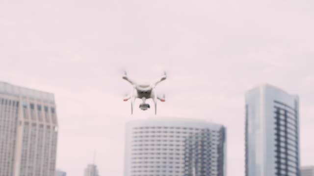 Quadcopter-drone-con-cámara-en-cardán-volando-en-el-cielo-de-la-ciudad-filmada-en-cámara-lenta
