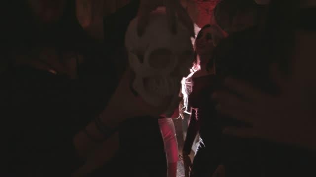 Mujer-joven-vampiro-sosteniendo-el-cráneo-y-bailando-en-fiesta-de-Halloween