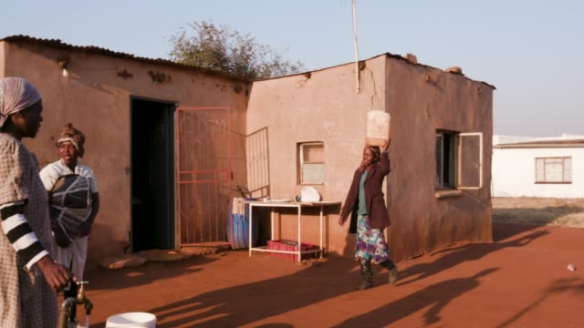 Mujer-africana-al-llegar-a-una-casa-para-recoger-agua-en-un-balde-plástico-mientras-que-otros-están-parados-en-línea-y-esperan-su-turno