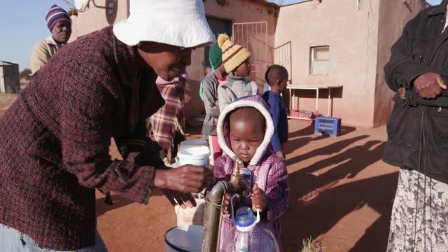 Niña-africana-recogiendo-agua-de-un-grifo-mientras-que-la-mujer-y-los-niños-en-fila-para-recoger-agua-en-envases-de-plástico-debido-a-la-sequía-en-África-del-sur
