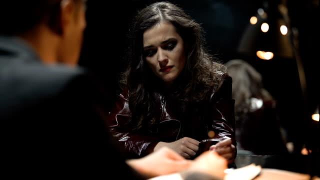 Detective-interrogando-a-mujer-señora-extinción-trozo-de-cigarrillo-llorando
