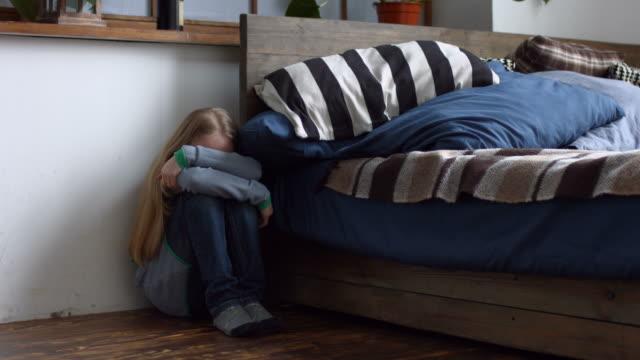Kleines-Mädchen-sitzt-im-Winkel-des-Zimmers-Angst