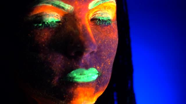 Retrato-de-moda-modelo-mujer-con-trenzas-de-luz-de-neón-de-cerca-Maquillaje-fluorescente-que-brilla-intensamente-bajo-luz-negra-ultravioleta-Club-de-noche-fiesta-halloween-psicodélico-conceptos