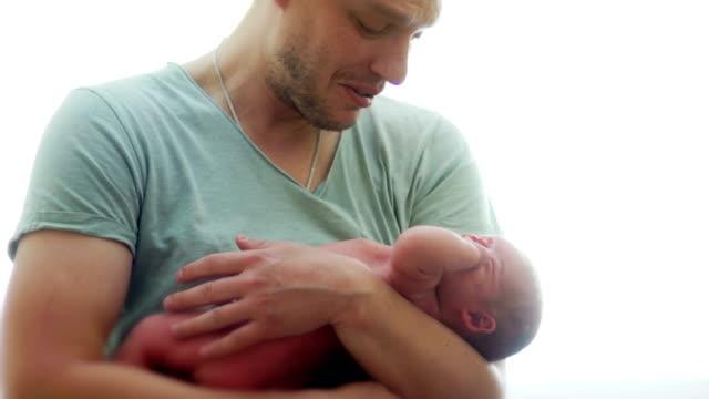 Ein-junger-Vater-beruhigt-ein-schreiendes-Neugeborenes-Baby-Das-nackte-Kind-liegt-in-den-Händen-eines-athletischen-Mannes-Zum-Vatertag-Tag-des-Kindes