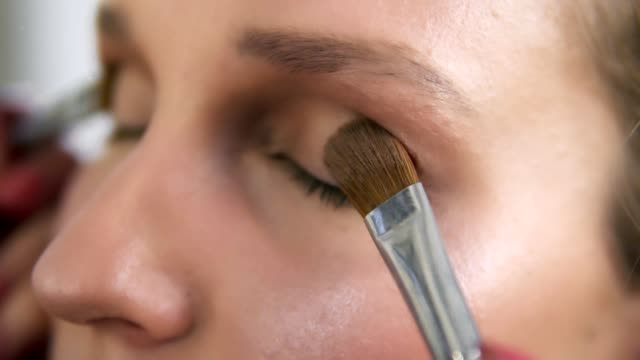 Make-up-artist-applying-light-brown-shadows-on-an-eyelids-with-two-brushes-together-Close-up-of-a-young-caucasian-woman-s-eyes