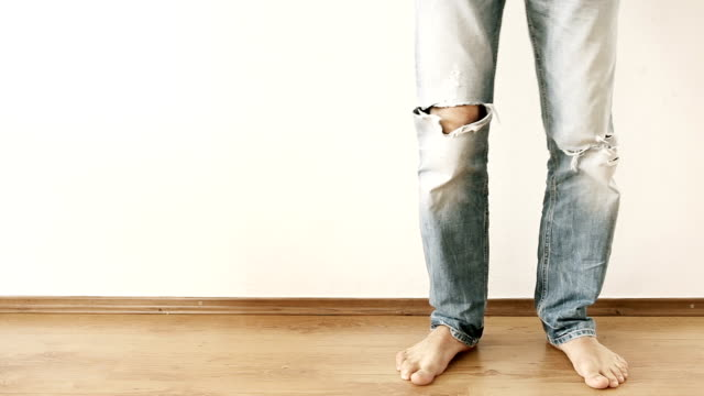 A-man-in-torn-up-jeans-stands-by-the-wall-and-stomps-with-his-foot